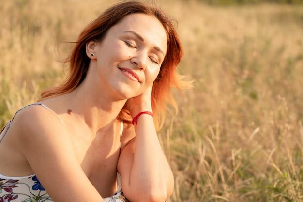 La bella ragazza dai capelli rossi tenera gode del tramonto in un campo con una collina.