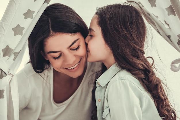 La bella ragazza della scuola e sua madre stanno parlando e sorridendo.