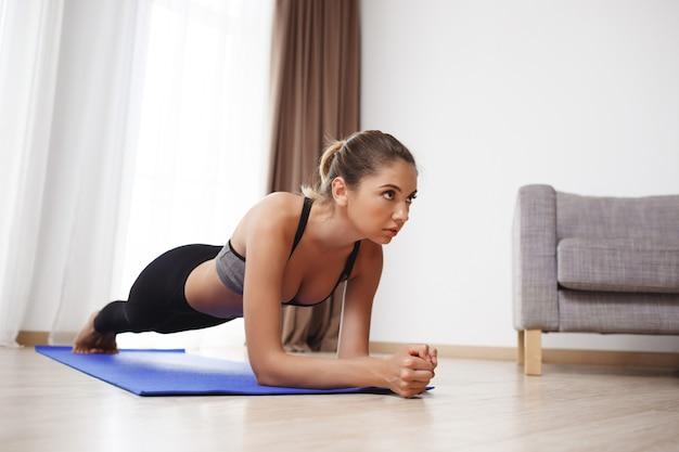 La bella ragazza di forma fisica fa gli esercizi della plancia sul pavimento