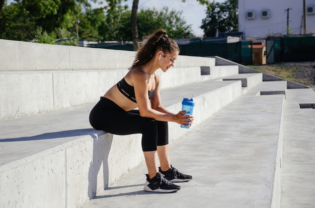 La bella ragazza di forma fisica si riposa tra l'allenamento all'aperto