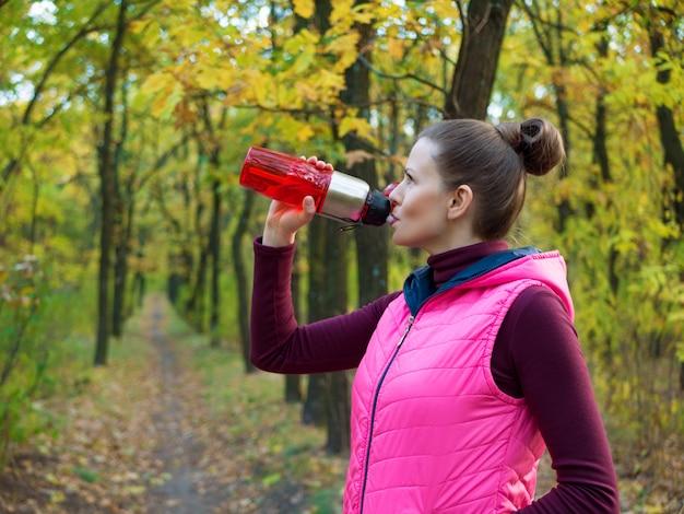 La bella ragazza di sport di forma fisica nel parco di autunno in abiti sportivi beve l'acqua o la bevanda isotonica da una bottiglia di sport.