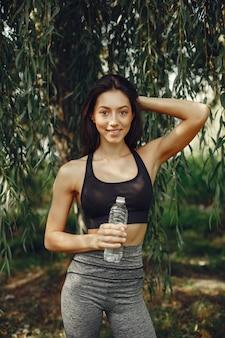La bella ragazza di sport in un parco dell'estate