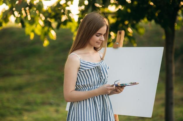 La bella ragazza disegna un'immagine nel parco usando una tavolozza con vernici e una spatola. cavalletto e tela con una foto.