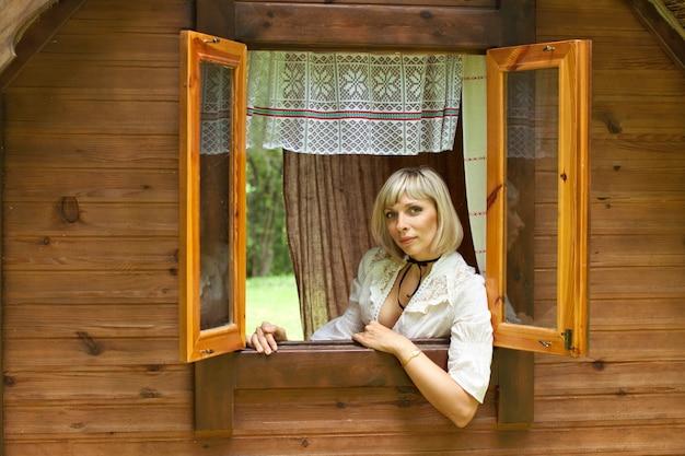 La bella ragazza europea guarda fuori dalla finestra