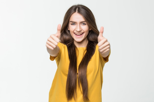 La bella ragazza felice che mostra i pollici aumenta il simbolo da due mani isolate sulla parete bianca