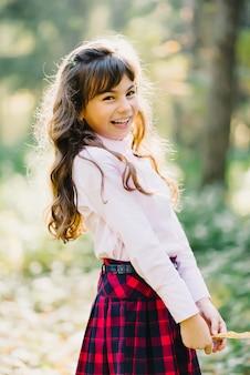 La bella ragazza felice del brunette dell'aspetto caucasico ride e sorride in autunno