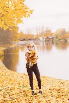 La bella ragazza getta sulle foglie di autunno. la giovane donna attraente sta riposando, scherzando