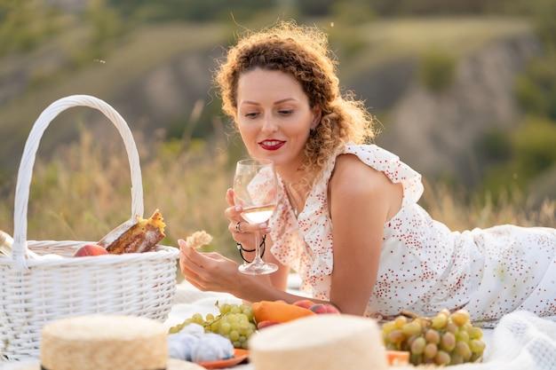 La bella ragazza gode di un picnic al tramonto in un bellissimo posto.