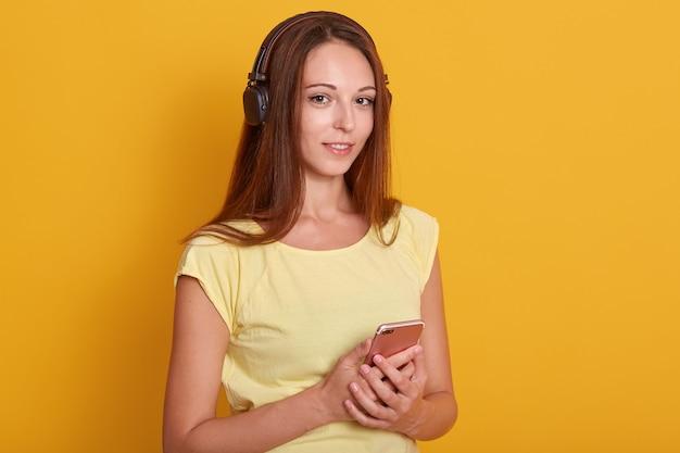 La bella ragazza ha vestito la musica d'ascolto della maglietta casuale bianca via le cuffie, tenendo lo smartphone in mani