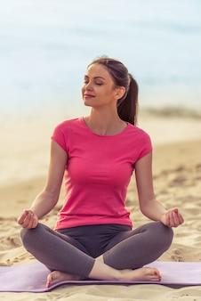 La bella ragazza in abiti sportivi sta meditando.