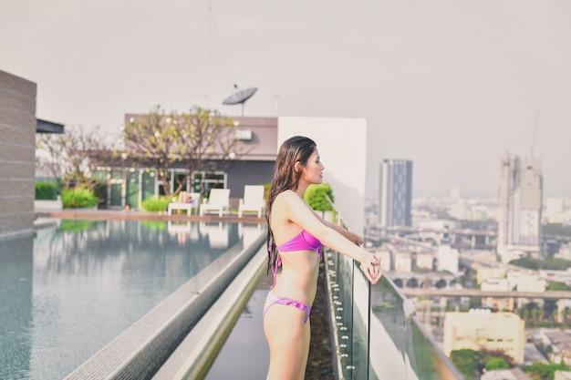 La bella ragazza in costume da bagno sta rilassando alla piscina.