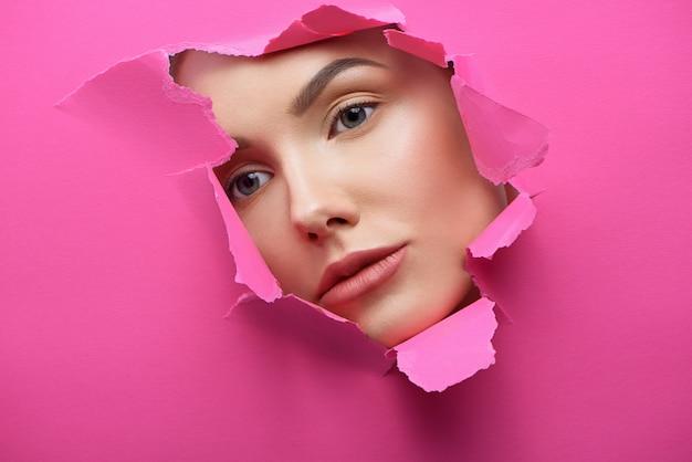 La bella ragazza in faccia nel buco del cartone rosa lacerato.