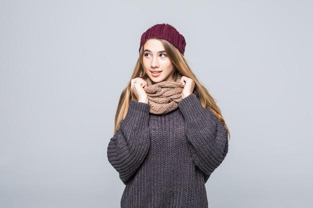La bella ragazza in maglione e sciarpa grigi è fredda sul grigio