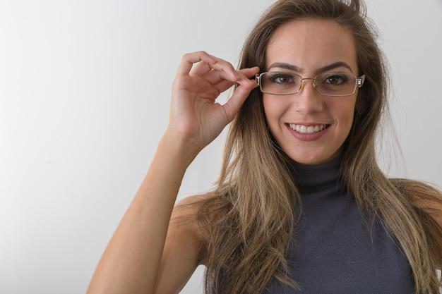 La bella ragazza in occhiali sta esaminando la macchina fotografica e sta sorridendo, su fondo grigio