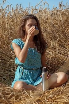 La bella ragazza in prendisole blu si siede sul campo di frumento e beve il tè o il caffè dalla boccetta del thermos