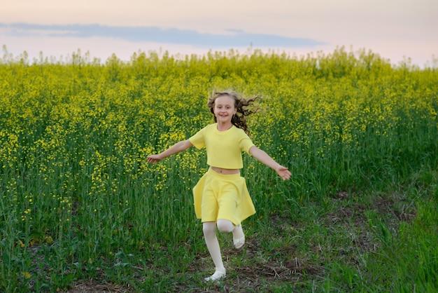 La bella ragazza in un abito giallo sul campo in fiore