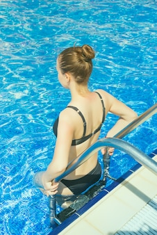 La bella ragazza in un costume da bagno viene in piscina