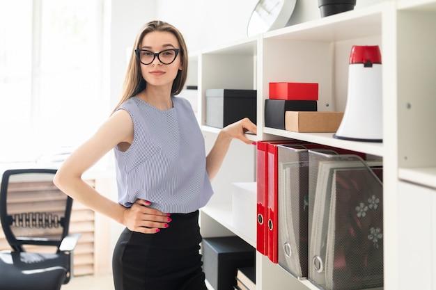 La bella ragazza in un ufficio sta vicino ad uno scaffale con i documenti.