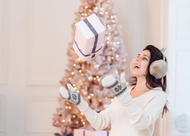 La bella ragazza in un vestito bianco genera un regalo.