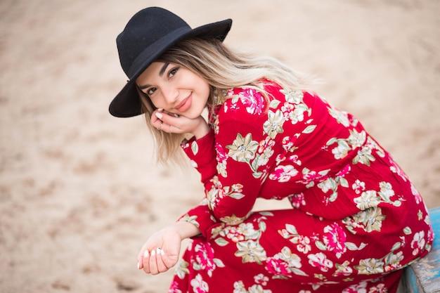 La bella ragazza in un vestito rosso e una giacca nera si siede su una barca blu