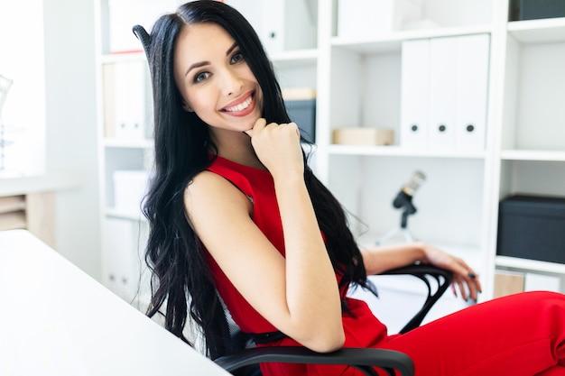 La bella ragazza in un vestito rosso sta sedendosi su una sedia nell'ufficio.