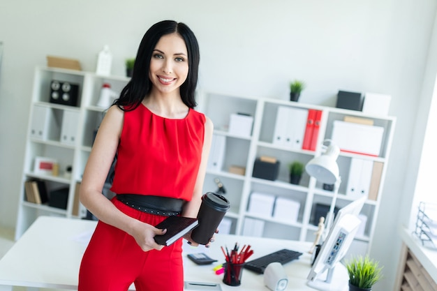 La bella ragazza in un vestito rosso sta stando nell'ufficio e sta tenendo un taccuino e un bicchiere di caffè.