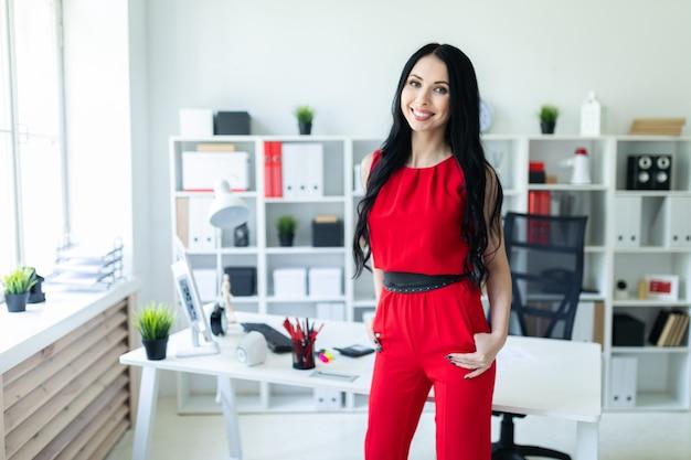 La bella ragazza in un vestito rosso sta stando nell'ufficio.