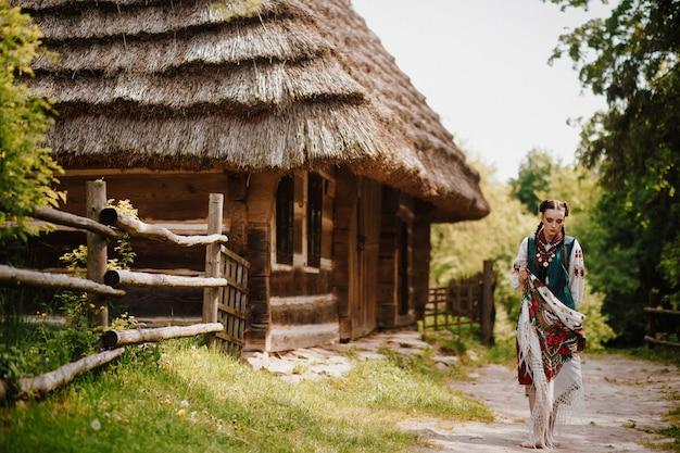 La bella ragazza in un vestito tradizionale colorato cammina intorno al villaggio