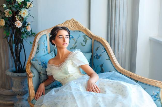 La bella ragazza in vestito ricco che si trova sul sofà, si rilassa il concetto