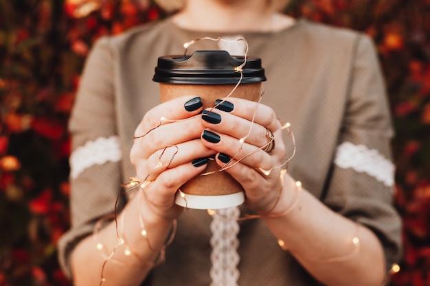 La bella ragazza in via di autunno tiene una tazza con una bevanda calda in sue mani con le luci. immagine di concetto