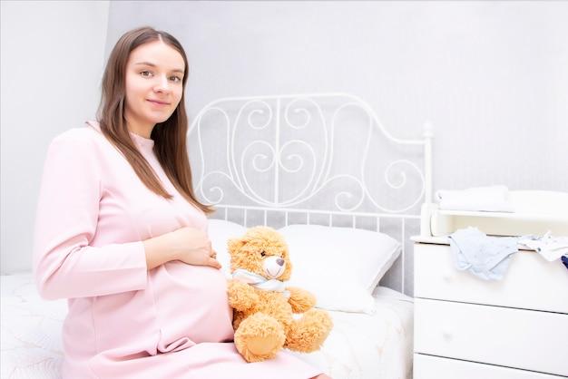La bella ragazza incinta è seduta sul letto e le sue mani sono sul suo stomaco.