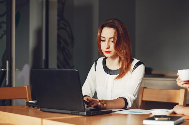 La bella ragazza lavora in ufficio