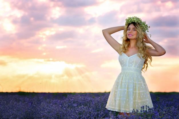 La bella ragazza nel giacimento della lavanda in vestito e fiori bianchi si avvolge