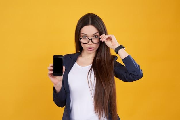 La bella ragazza propone con il telefono mobile nero isolato.