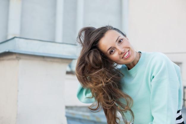 La bella ragazza raddrizza i suoi capelli