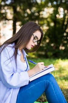 La bella ragazza seria dai capelli scuri in giacca di jeans e occhiali scrive in taccuino nel parco