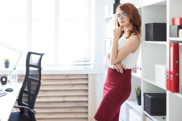 La bella ragazza si leva in piedi nell'ufficio vicino ad uno scaffale con i documenti.