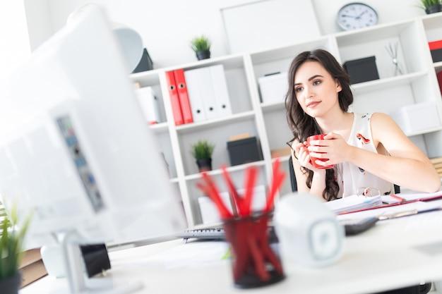 La bella ragazza si siede alla scrivania, guarda lo schermo del computer e tiene in mano una tazza rossa.