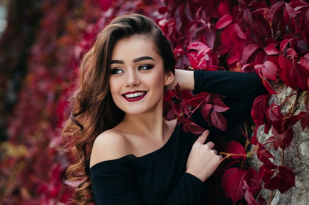 La bella ragazza si trova vicino walll con foglie