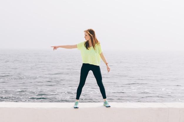 La bella ragazza sottile in abiti sportivi verdi mostra la direzione della mano sullo sfondo del mare