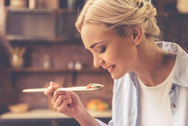 La bella ragazza sta assaggiando il cibo e sta sorridendo mentre cucinava.