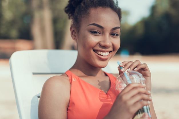 La bella ragazza sta bevendo il cocktail e sta ridendo
