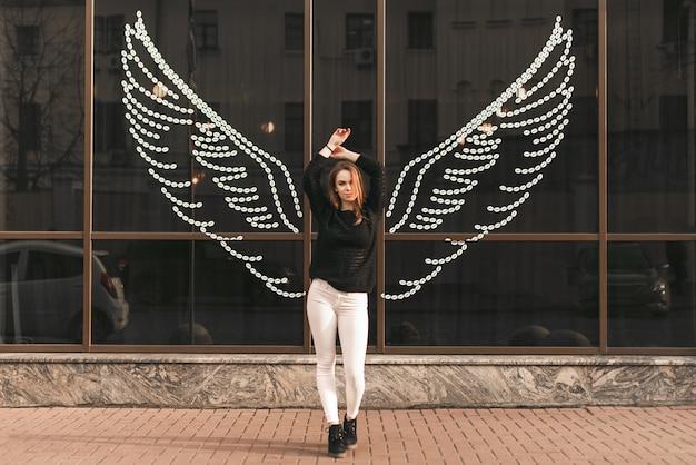 La bella ragazza sta con le sue mani sollevate sullo sfondo di un muro scuro in cui le ali sono disegnate, guardando a porte chiuse e in posa