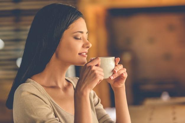 La bella ragazza sta godendo l'aroma del caffè
