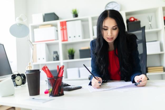 La bella ragazza sta lavorando con i documenti nell'ufficio al tavolo e sta tenendo una matita