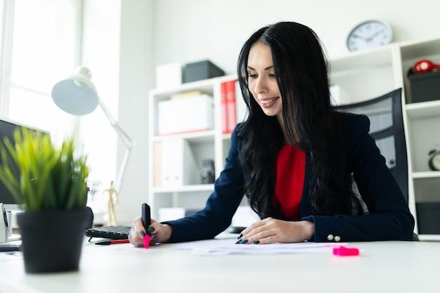 La bella ragazza sta lavorando con i documenti nell'ufficio al tavolo.