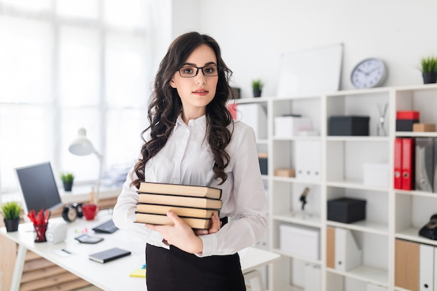 La bella ragazza sta nell'ufficio e tiene una pila di libri in sue mani.