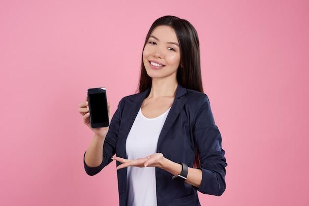 La bella ragazza sta proponendo con il telefono nero