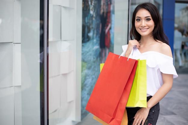 La bella ragazza sta tenendo i sacchetti della spesa e sta sorridendo mentre faceva la spesa nel supermercato / centro commerciale