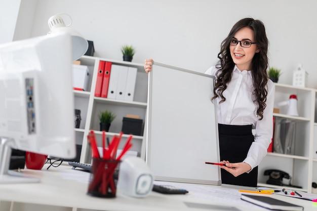 La bella ragazza sta vicino ad una scrivania e indica con una penna un bordo vuoto.